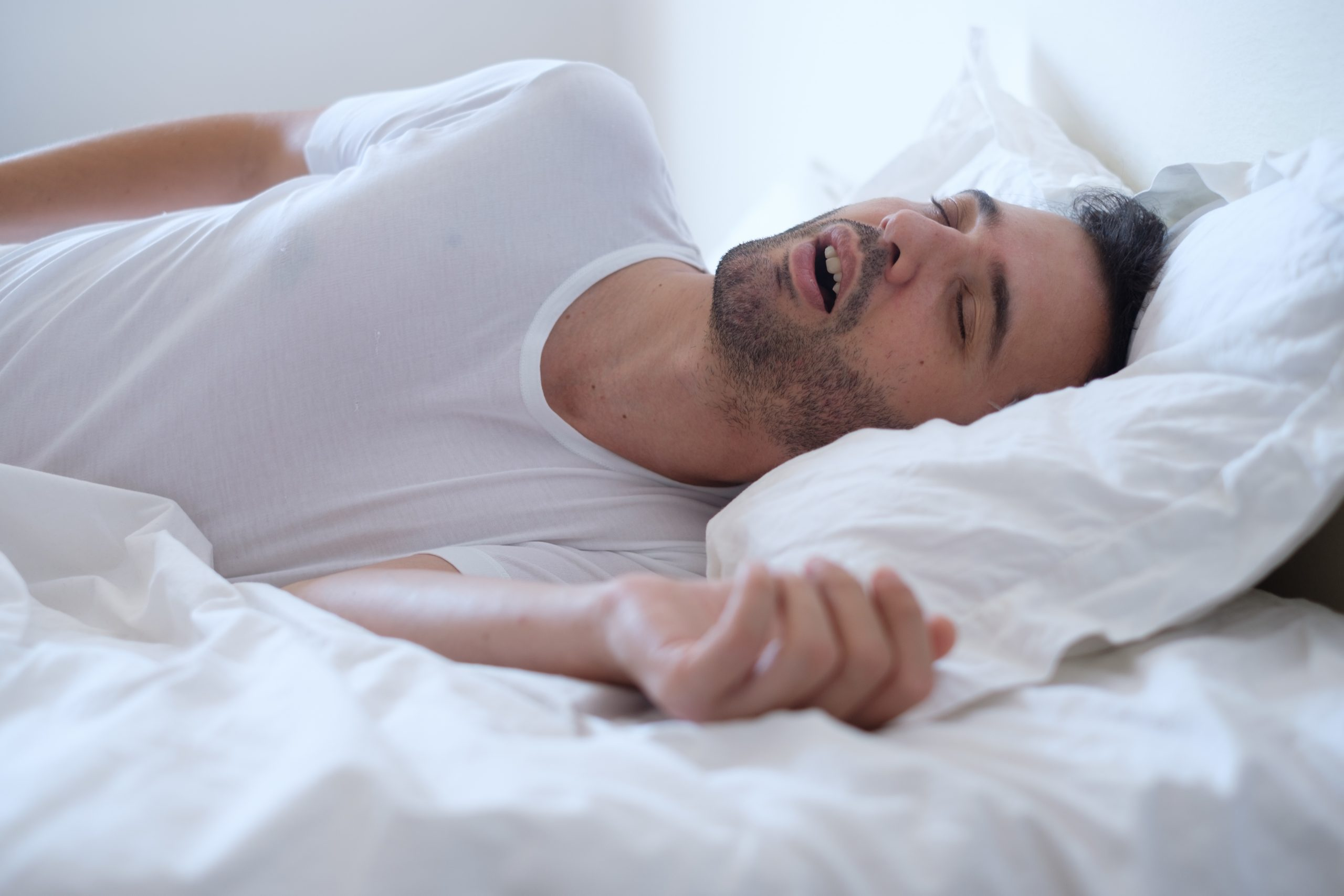 Man snoring because of apnea lying in the bed