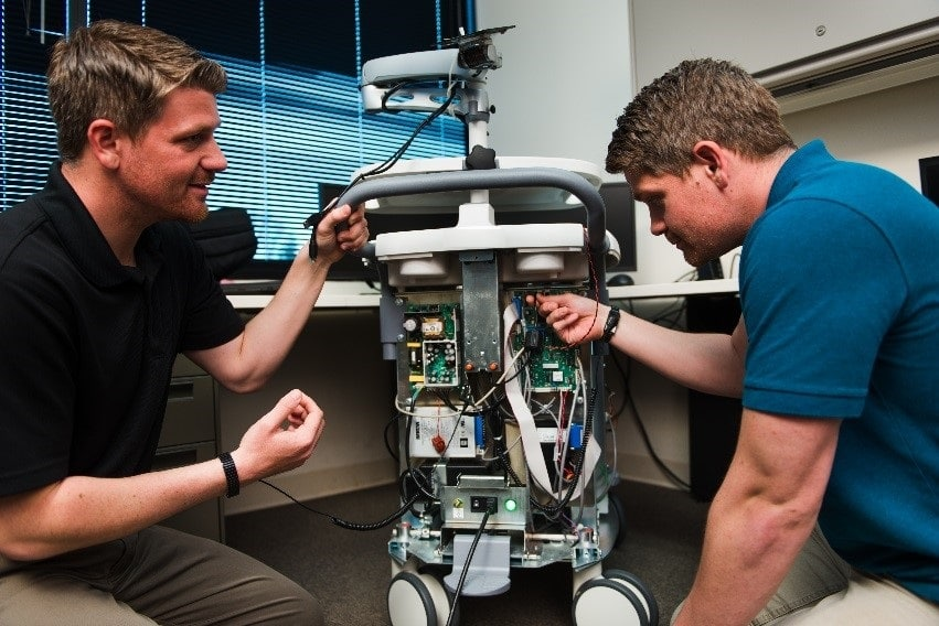 people working on a mechanical device