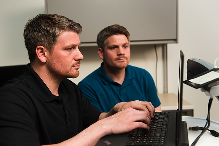 Two men looking and typing on a computer